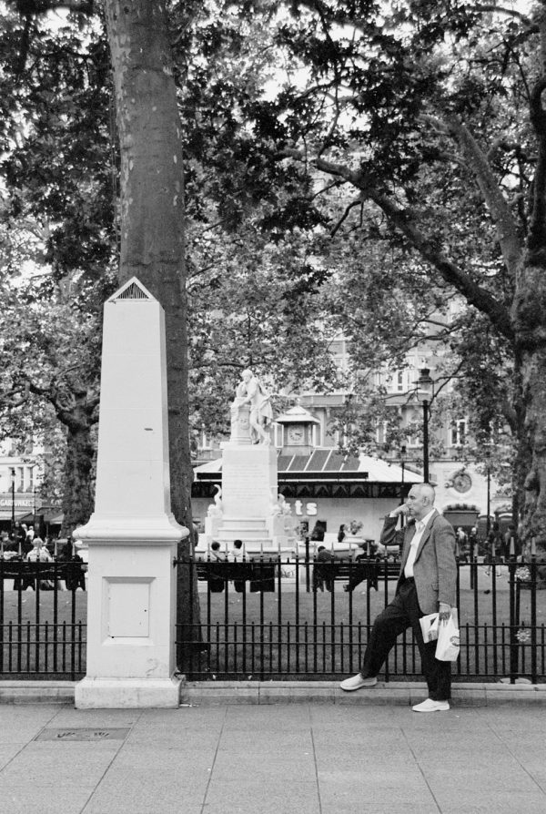Black and White, Photograph, Cliche, Man Standing in Front of Statue, London, 2003